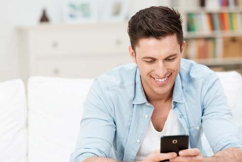 Man smiling ad he reads a text message on his mobile while relaxing at home on a couch in the living room